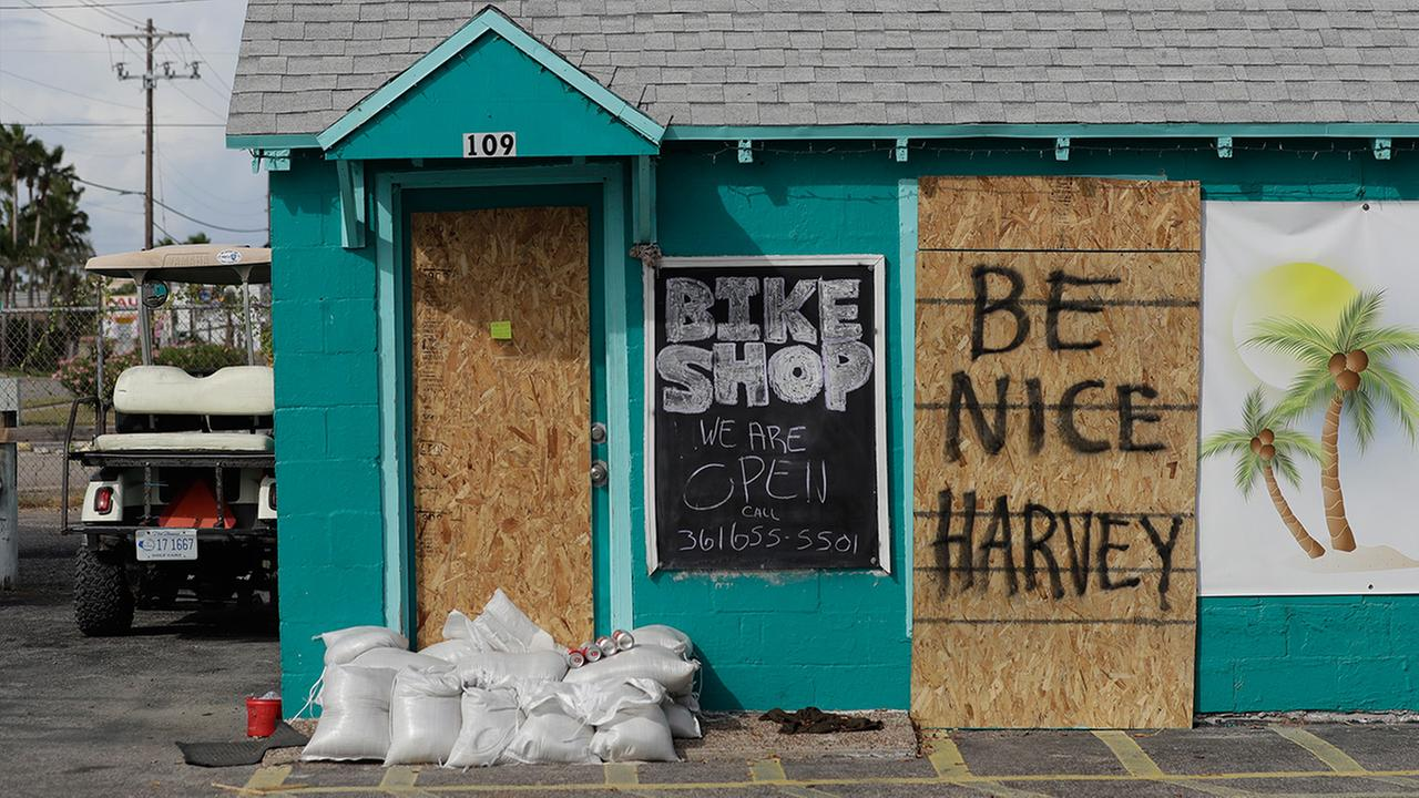 A sign reading Be Nice Harvey was left behind on a boarded up business