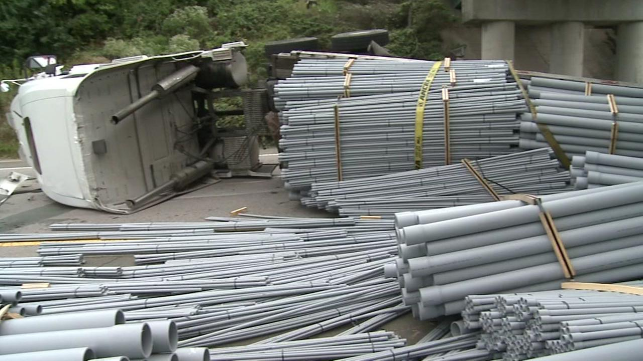 Truck carrying pipes overturns
