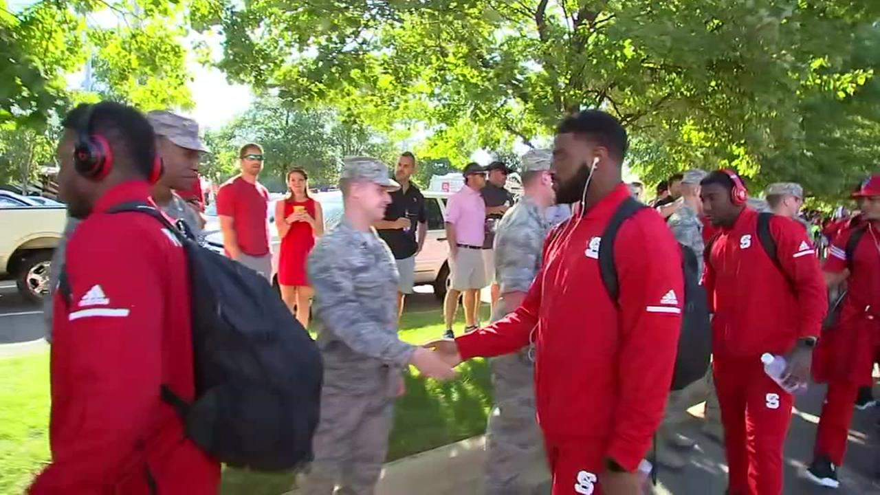 NC State football players shake hands of military personnel on hand for military day.