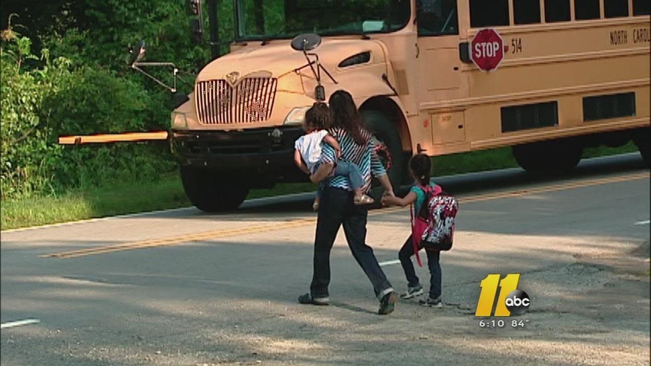 Parent walks kids across street to stopped school bus