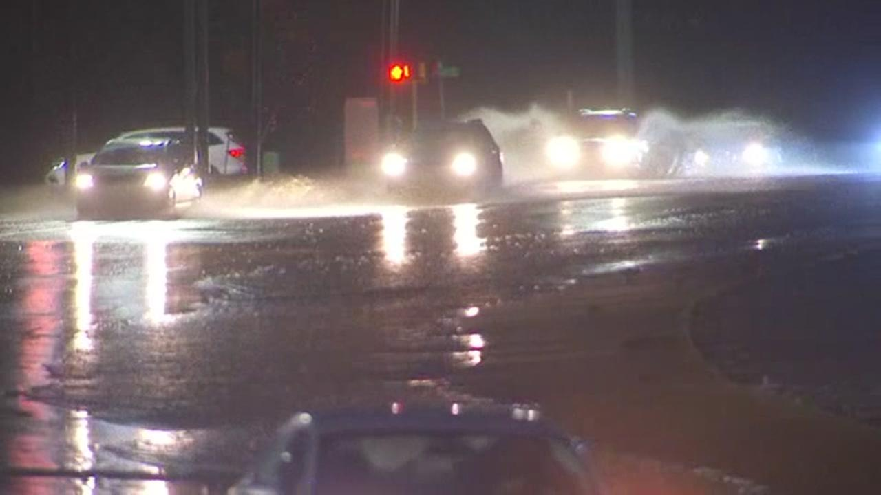 Cars drive through drenched Raleigh streets