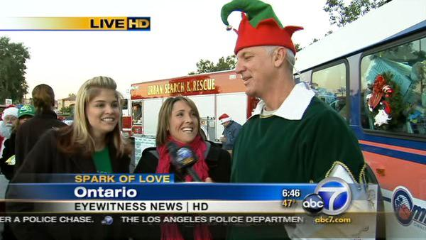 Women join Garth the Elf to donate toys