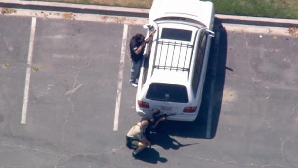 In this photo, police are seen in a Long Beach parking in a tactical position after cornering an armed-robbery suspect that led them on a chase from Redlands to Long Beach, Monday, June 21, 2010.