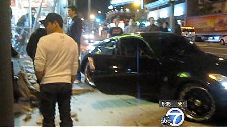 People stand at the scene of a hit and run in West Hollywood that caused major damage to a liquor store.