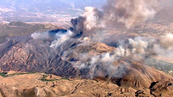 An aerial shot shows smoke from the hillsides of Beaumont where a major brush fire burned on Saturday, June 16, 2012. The