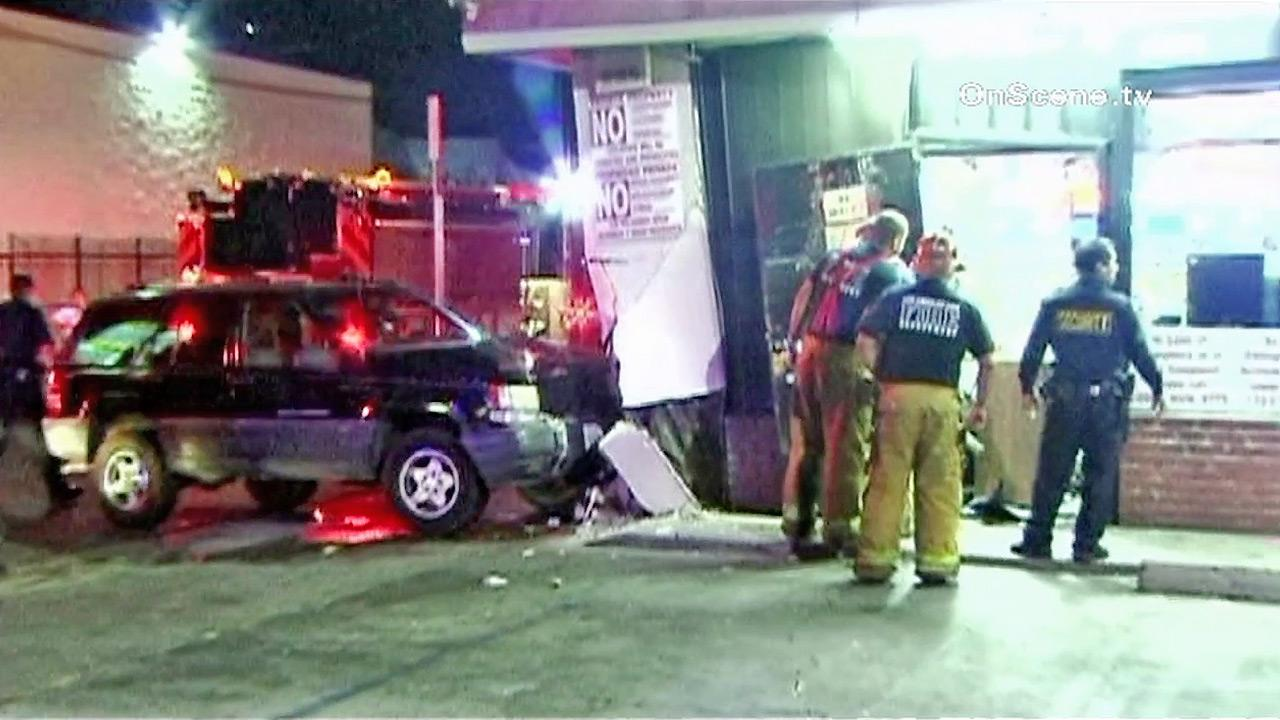 Authorities are seen at the site of a car that crashed into a liquor store in South Los Angeles during a carjacking attempt on Monday, Oct. 2, 2012.