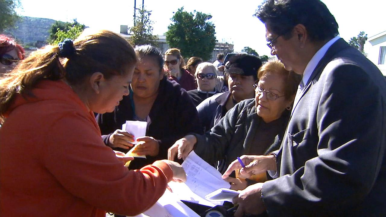 Residents of Brookside Mobile Country Club in El Monte show Eyewitness News reporter Sid Garcia documents outlining sharp rent hikes on their spaces Tuesday, Jan. 29, 2013.