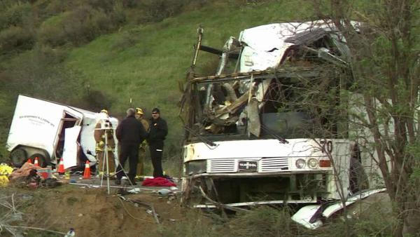 Investigators are seen combing through the wreckage of a tour bus crash on State Route 38 near Yucaipa that killed eight people and injured 38 others Sunday, Feb