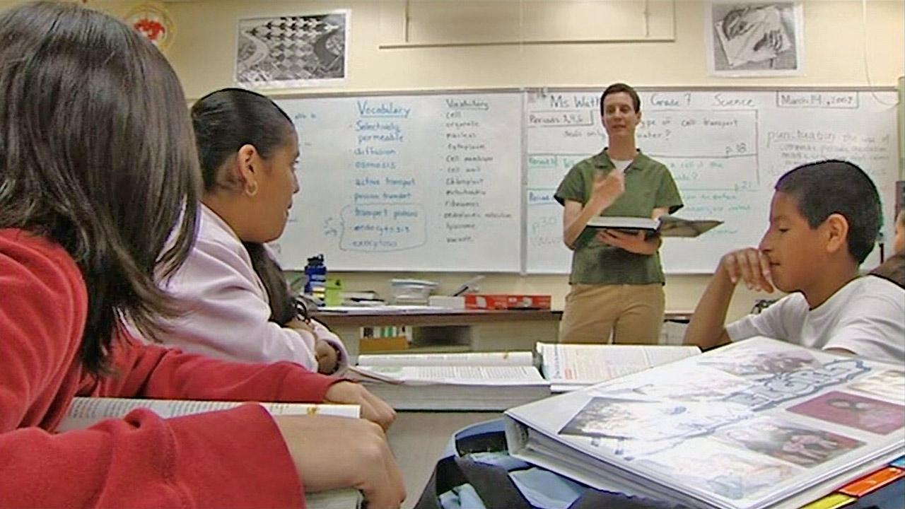 A teacher is seen with students in a classroom.