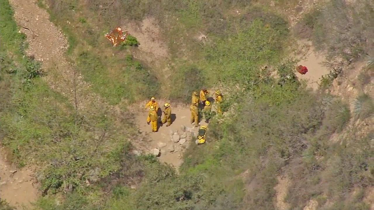 Firefighters are seen in Eaton Canyon where two hikers fell on Friday, March 22, 2013. One of the hikers died and the other was hospitalized.