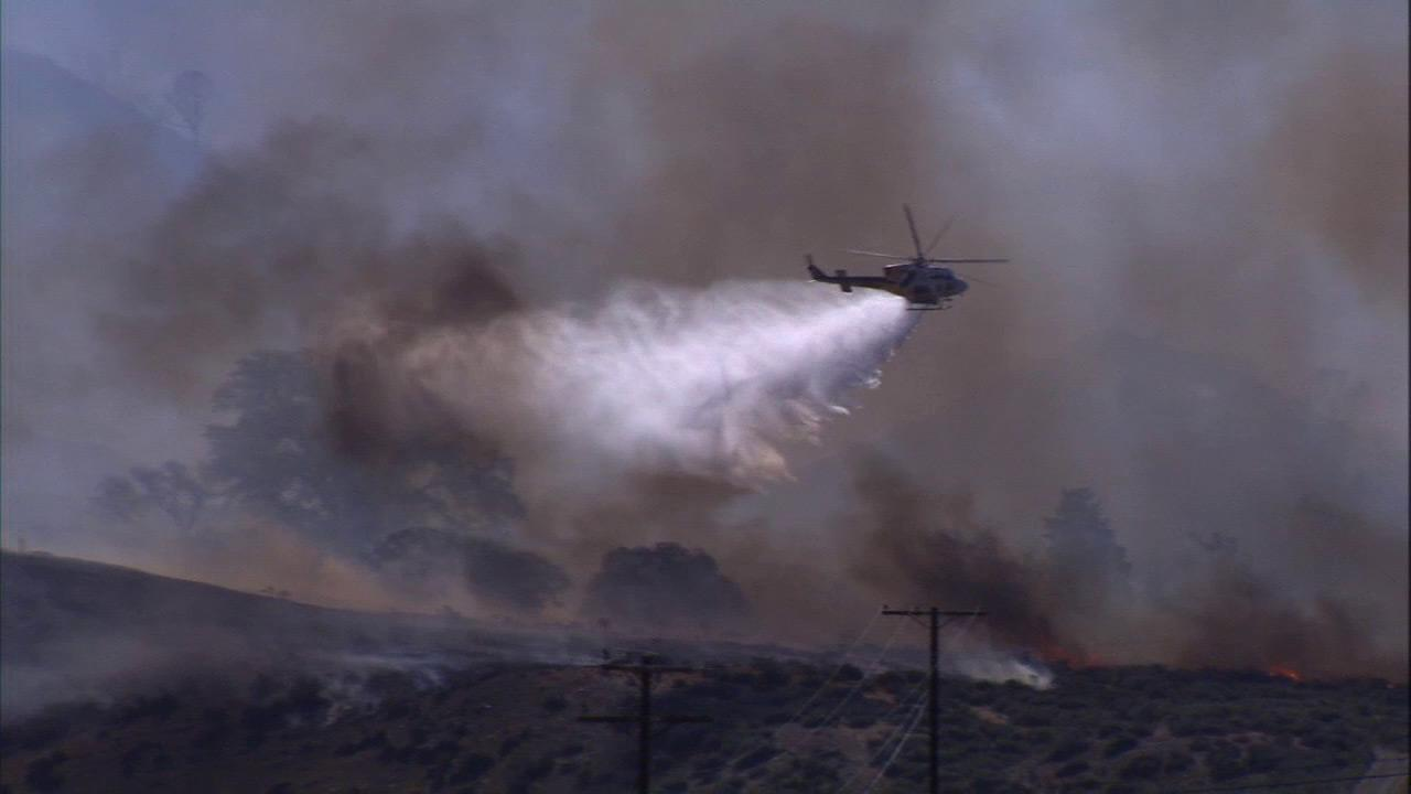 An aircraft makes a drop on flames in the Frazier Park fire.
