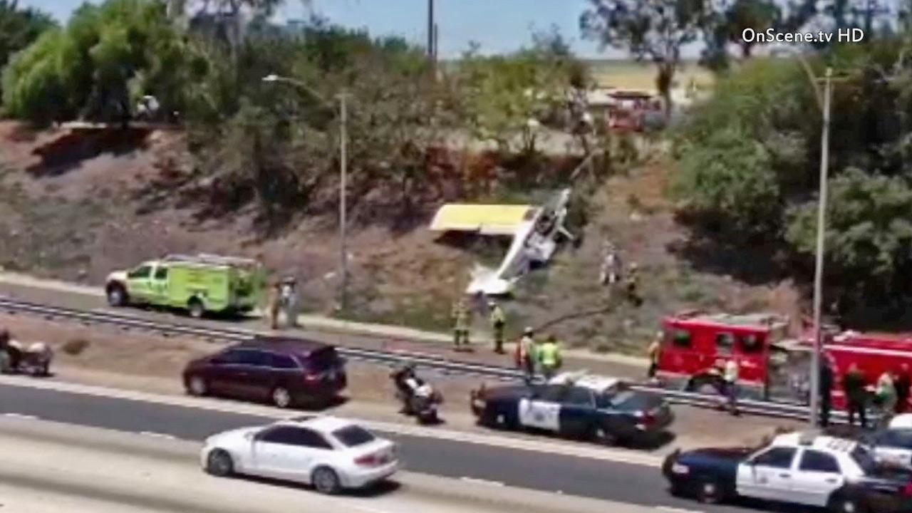 Crews are seen after a small plane made a crash landing on the shoulder of the 405 Freeway in Long Beach on Saturday, July 6, 2013.