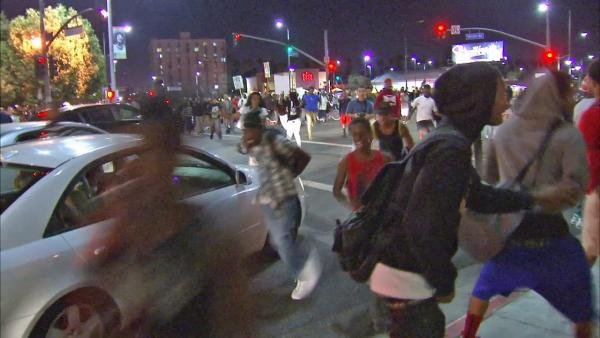 Protesters run through an intersection of the Crenshaw District of Los Angeles on Monday, July 15, 2013, during an unruly demonstration against the acquittal of George Zimmerman.