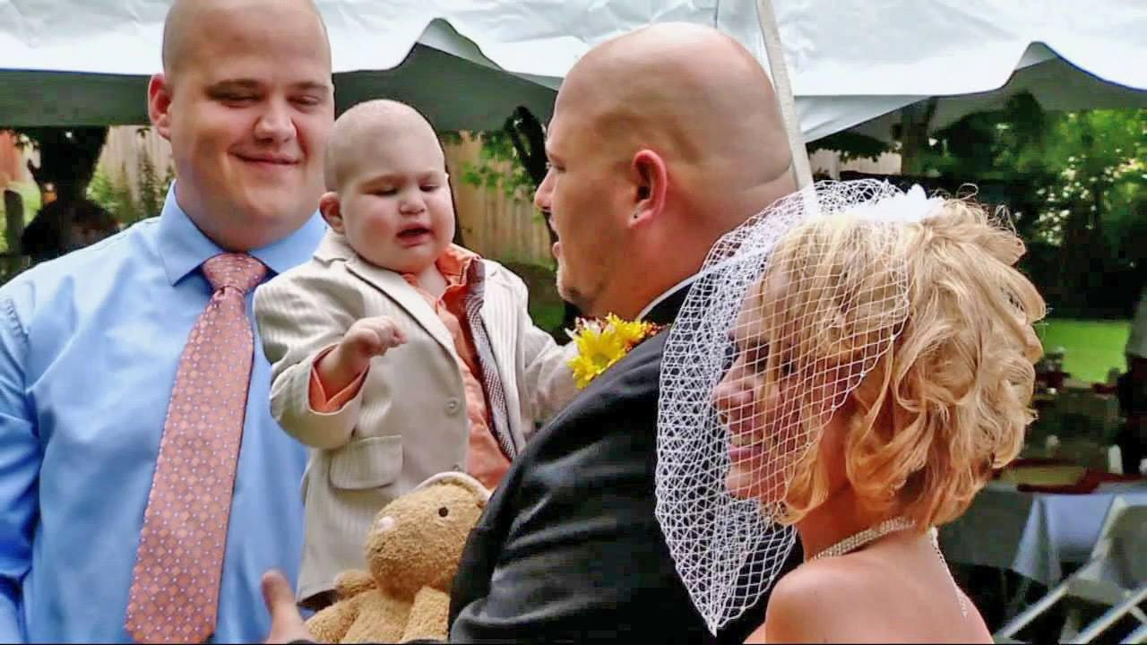 Logan Stevenson, 2, is held by his father as his mother looks on during a wedding ceremony Saturday, Aug. 3, 2013. Logan died Monday, Aug. 5, 2013. He had leukemia and other complications.