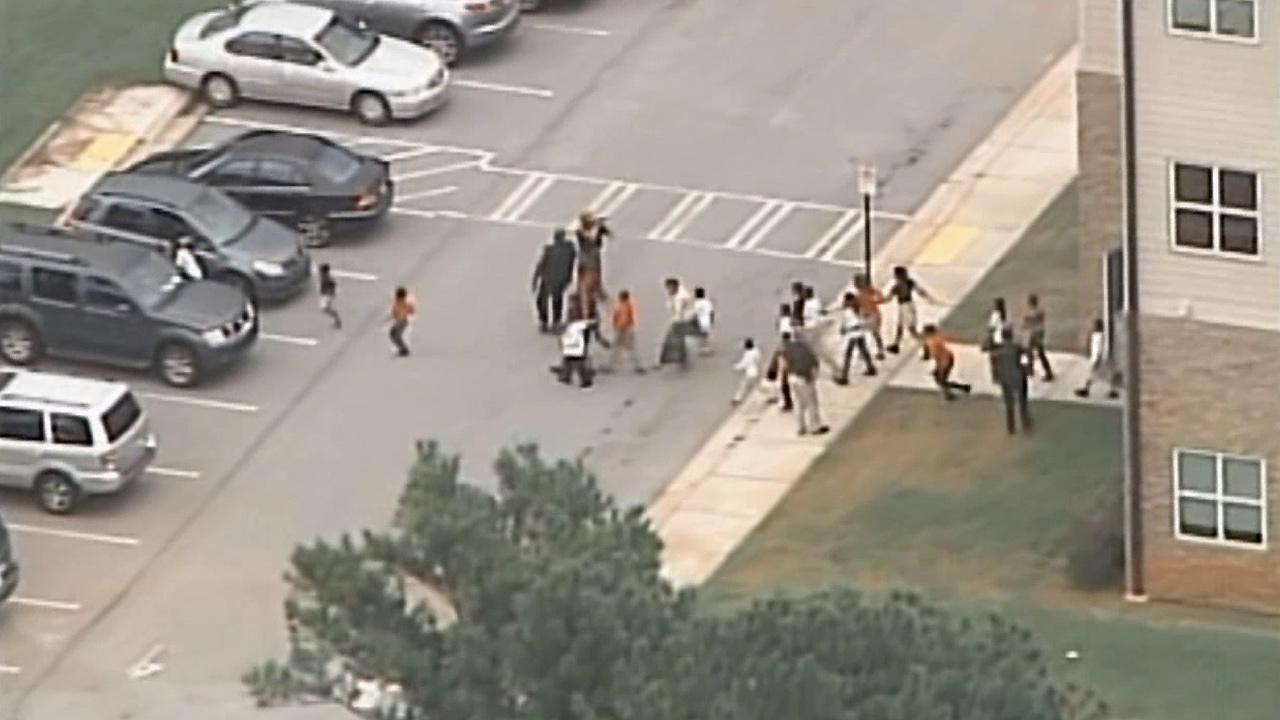 Students are evacuated from Ronald E. McNair Discovery Learning Academy in Decatur, Ga., after gunfire was reported at the school Tuesday, Aug. 20, 2013.