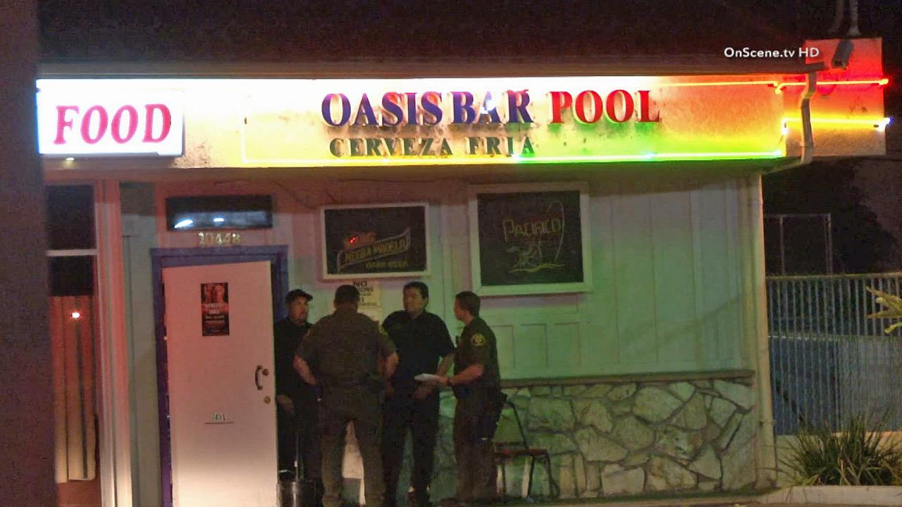 Authorities are seen outside the Oasis Bar in Stanton, where a man was shot and killed Sunday, September 15, 2013.