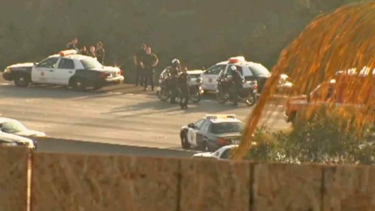 Officers are seen on a freeway where an officer was shot in San Diego on Thursday, Oct. 24, 2013.
