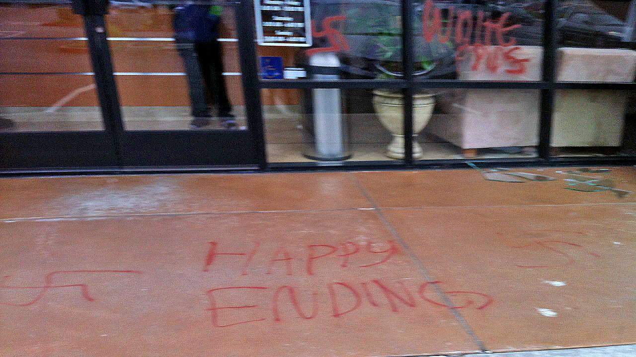 Graffiti of swastikas and a message that reads happy endings is seen on the property outside Massage Envy in Seal Beach Sunday, Oct. 27, 2013.