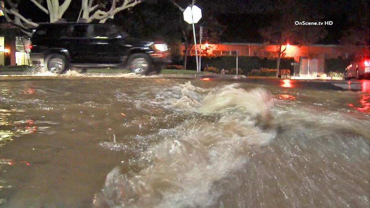 Cars drive in a street flooded by one of two water main breaks in Brentwood on Wednesday, Oct. 30, 2013.