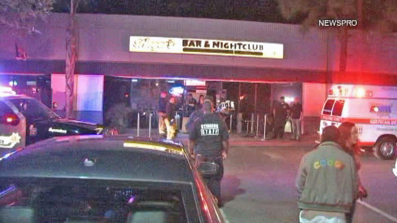 People are seen outside of Stingers Bar and Nightclub in San Bernardino after two people were shot Friday, Nov. 8, 2013.