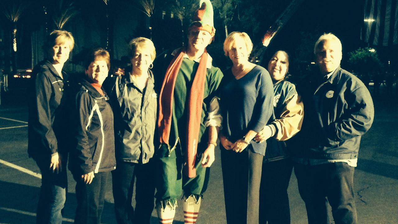 Employees from ABC Unified stand with Garth the Elf at Stuff-a-Bus in Cerritos on Friday, Nov. 22, 2013.