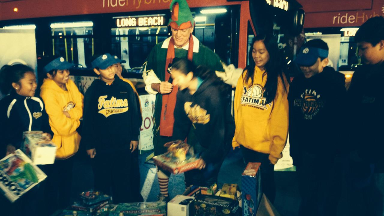 Students from Our Lady of Fatima School help Garth the Elf at Stuff-a-Bus in Cerritos on Friday, Nov. 22, 2013.