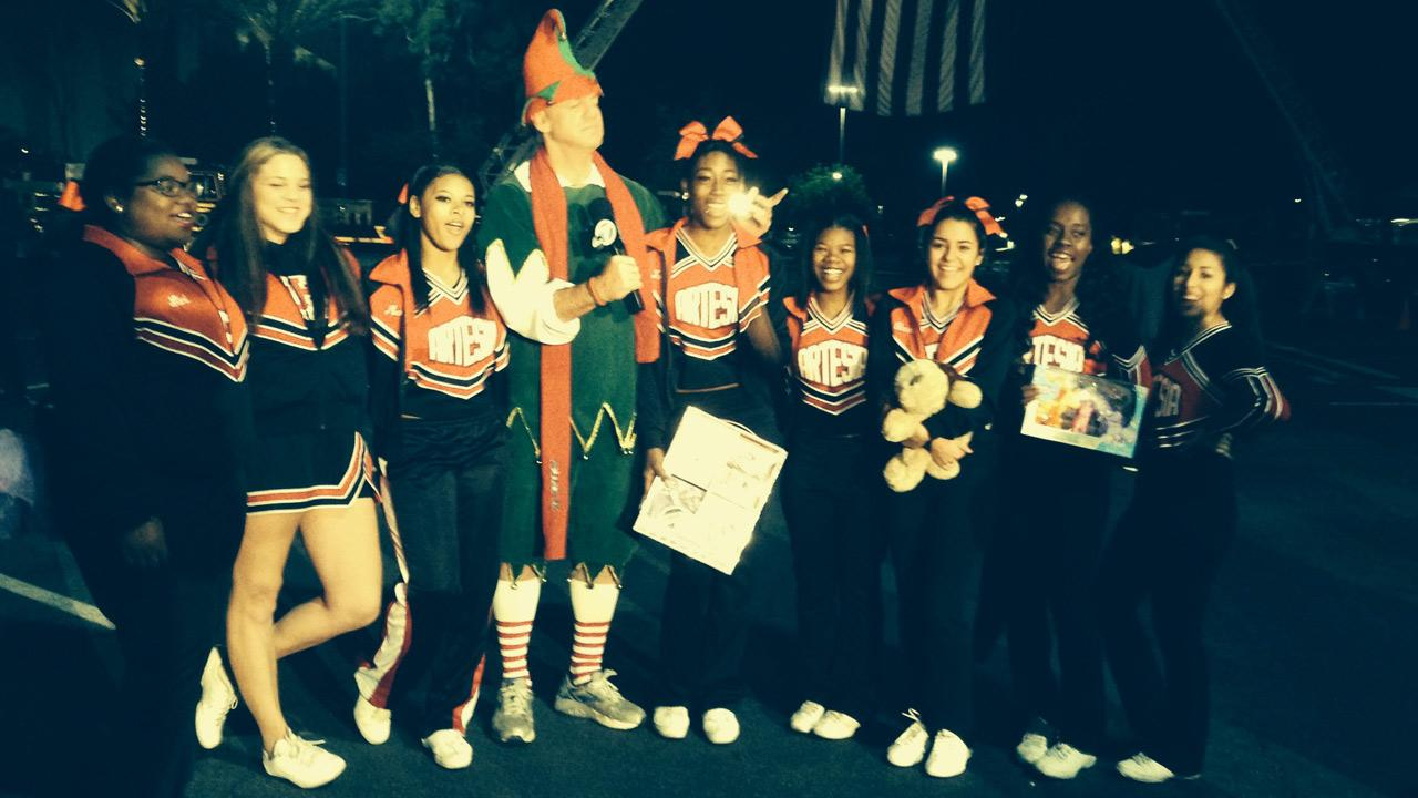 Artesia High School cheerleaders pose with Garth the Elf at Stuff-a-Bus in Cerritos on Friday, Nov. 22, 2013.