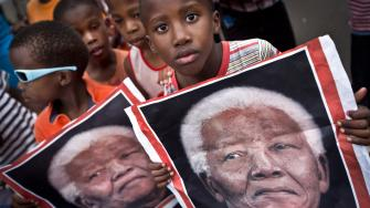 South African children hold placards showing the face of Nelson Mandela as they celebrate his life, in the street outside his old house in Soweto, Johannesburg, South Africa, Friday, Dec. 6, 2013.