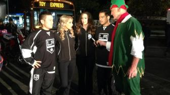 Garth the elf talks to members of the L.A. Kings Ice Crew at the Stuff-A-Bus event in Canoga Park on Friday, Dec. 13, 2013.