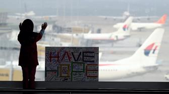 A girl stands next to a sign board made and written by the public at Kuala Lumpur International Airport in Sepang, Malaysia, Monday, March 10, 2014.