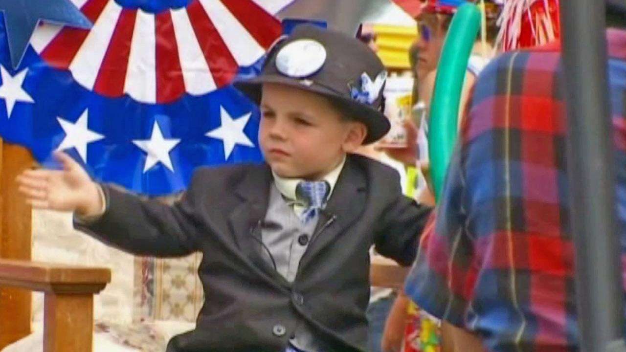 Mayor Bobby Tufts, 4, is shown waving to a crowd in the northern Minnesota town of Dorset.