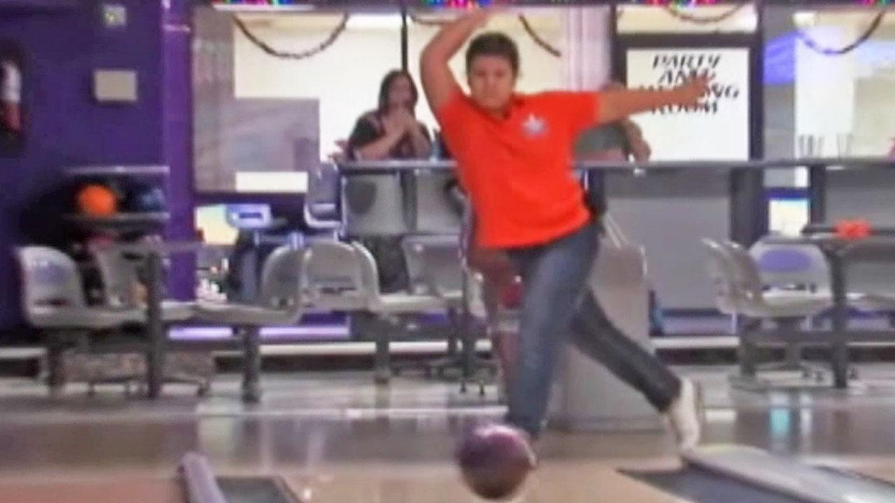 Hannah Diem, 9, strikes a pose after throwing a bowling ball. Diem became the youngest person to ever bowl a perfect 300.