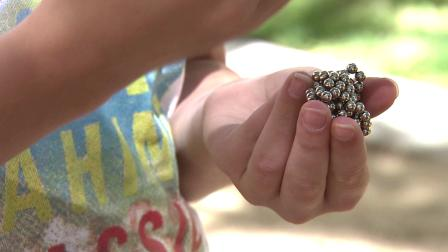 A child holds Buckyballs, the tiny, magnetic pellets intended to relieve stress, on Tuesday, July 17, 2012.