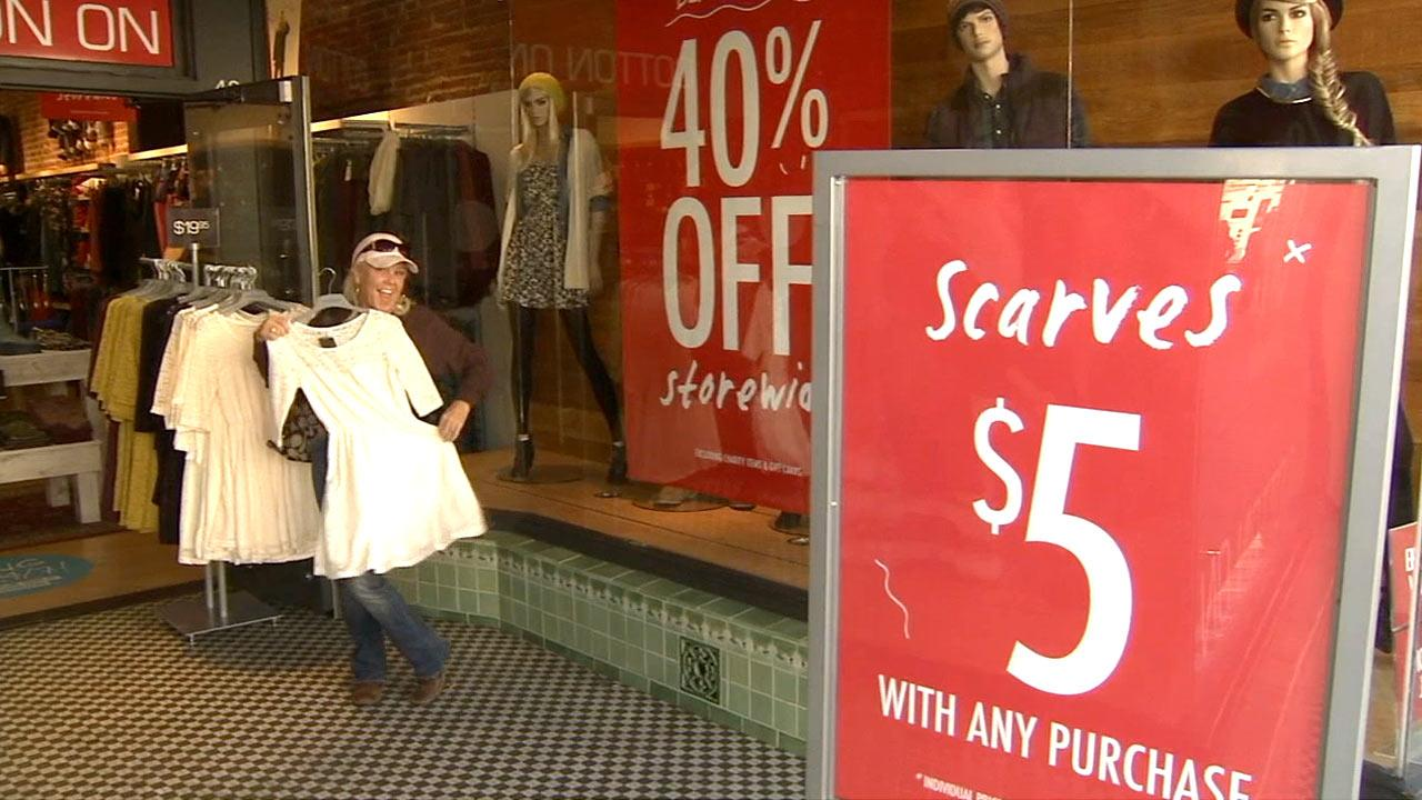 A shopper holds up a dress during a Black Friday sale at a local store on Friday, Nov. 23, 2012.
