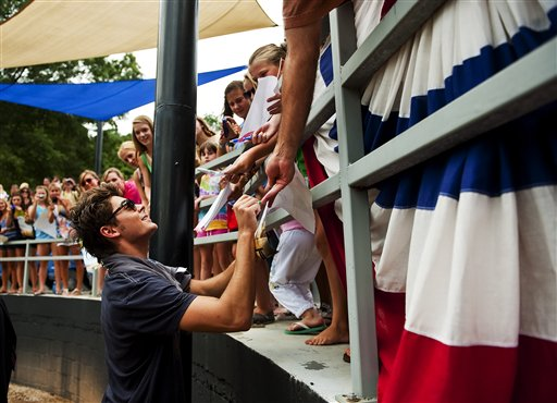 In this publicity image released by Allied Integrated Marketing, actor Zac Efron signs autographs for fans as he promotes his new film &#39;Charlie St. Cloud&#39; at the Dan Perez Baseball Camp at Murphey Candler Baseball Park on Tuesday, July 13, 2010, in Atlanta.  <span class=meta>(Allied Integrated Marketing, Pouya Dianat)</span>