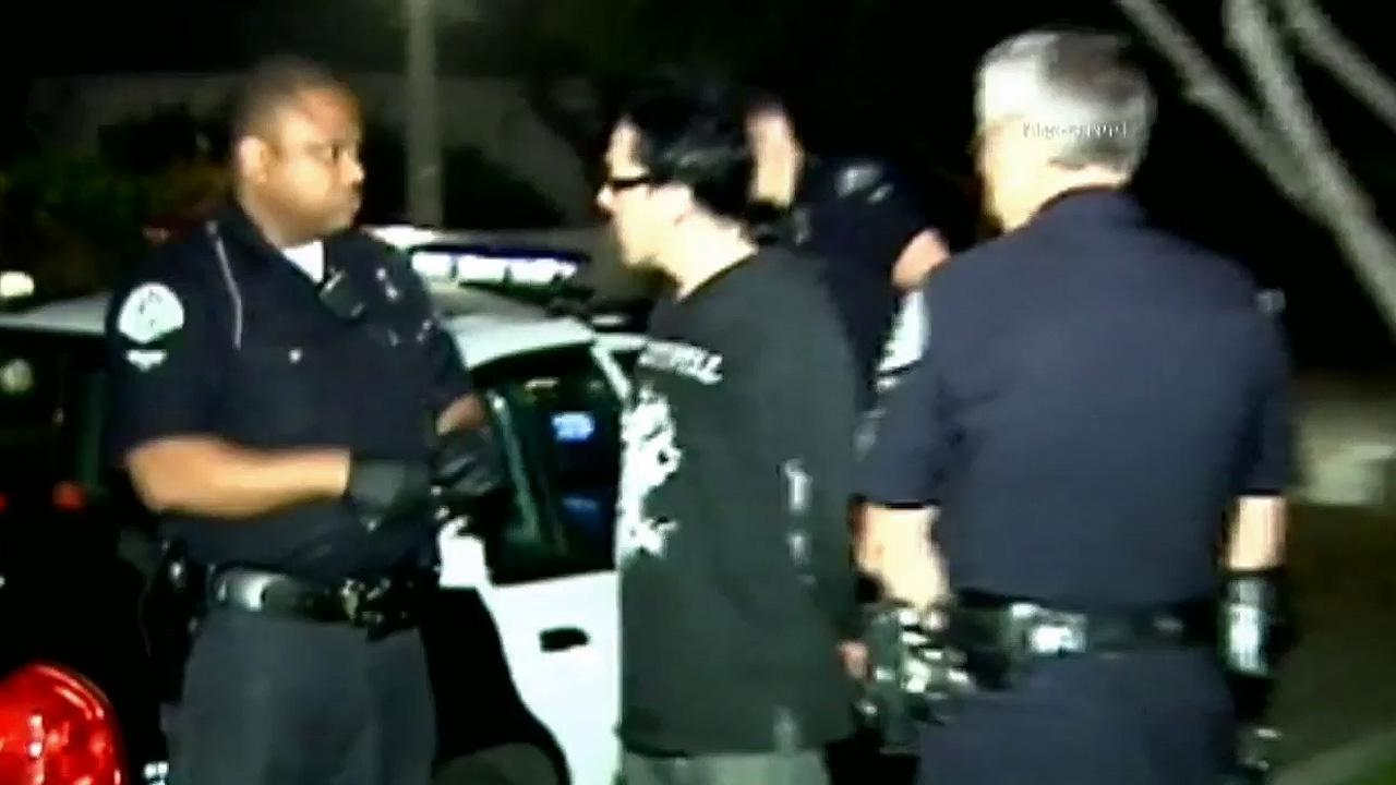 Police officers detain Karim Chmielinski, a member of the punk band Amen, on suspicion of driving under the influence on Friday, July 6, 2012.