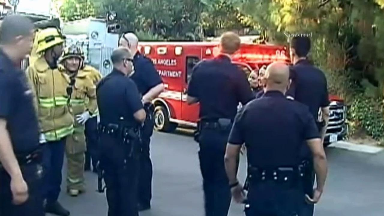 Police and firefighters are seen outside the home of Miley Cyrus on Wednesday, Aug. 1, 2012.