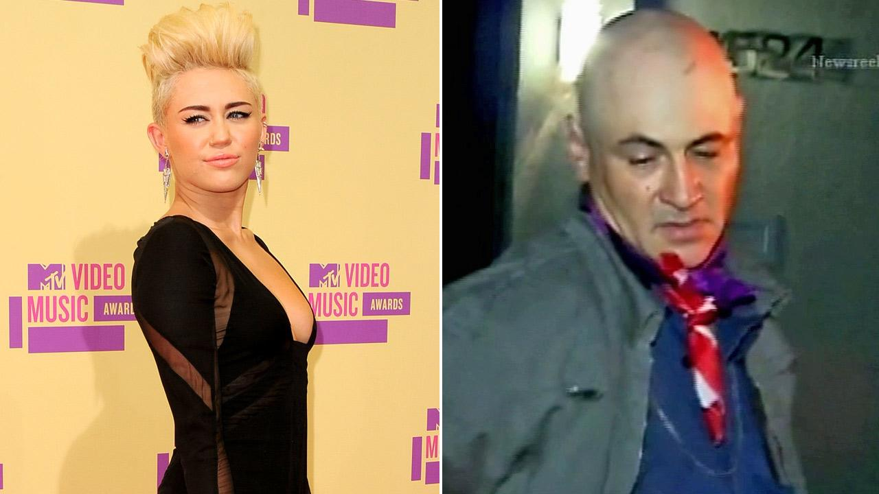 A suspect is detained by police Saturday, Sept. 8, 2012 after he allegedly made his way onto the Studio City property of singer Miley Cyrus, seen on the left at the MTV Video Music Awards on Thursday, Sept. 6, 2012.