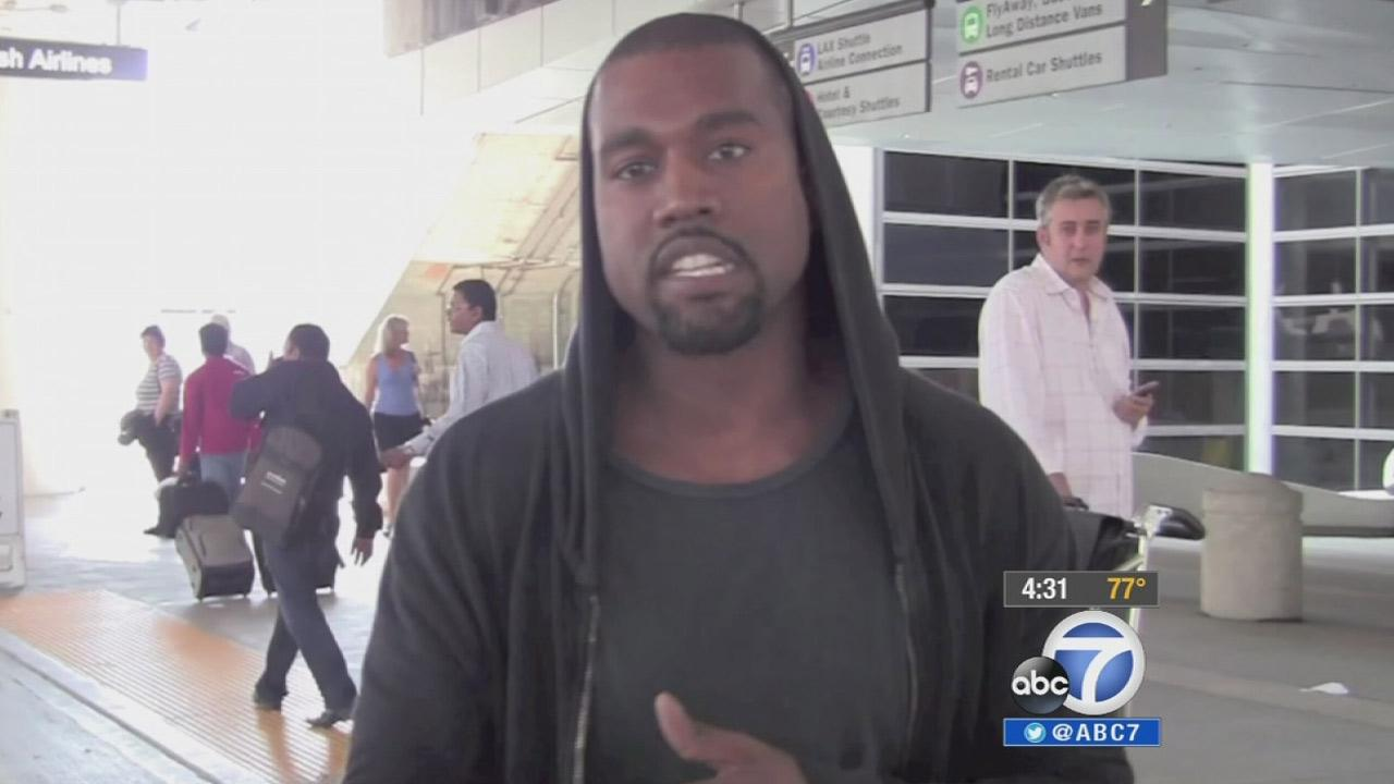 Rapper Kanye West is shown in a confrontation with a celebrity photographer at Los Angeles International Airport on July 19, 2013.k