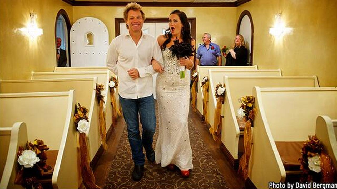 Singer Jon Bon Jovi, left, walks fan Branka Delic, right, down the aisle to give her away at her wedding in Las Vegas on Saturday, Oct. 12, 2013.