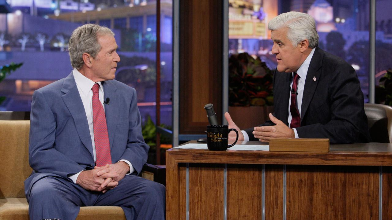 This Nov. 19, 2013 photo released by NBC shows former President George W. Bush, left, with host Jay Leno during The Tonight Show with Jay Leno, in Burbank, Calif.