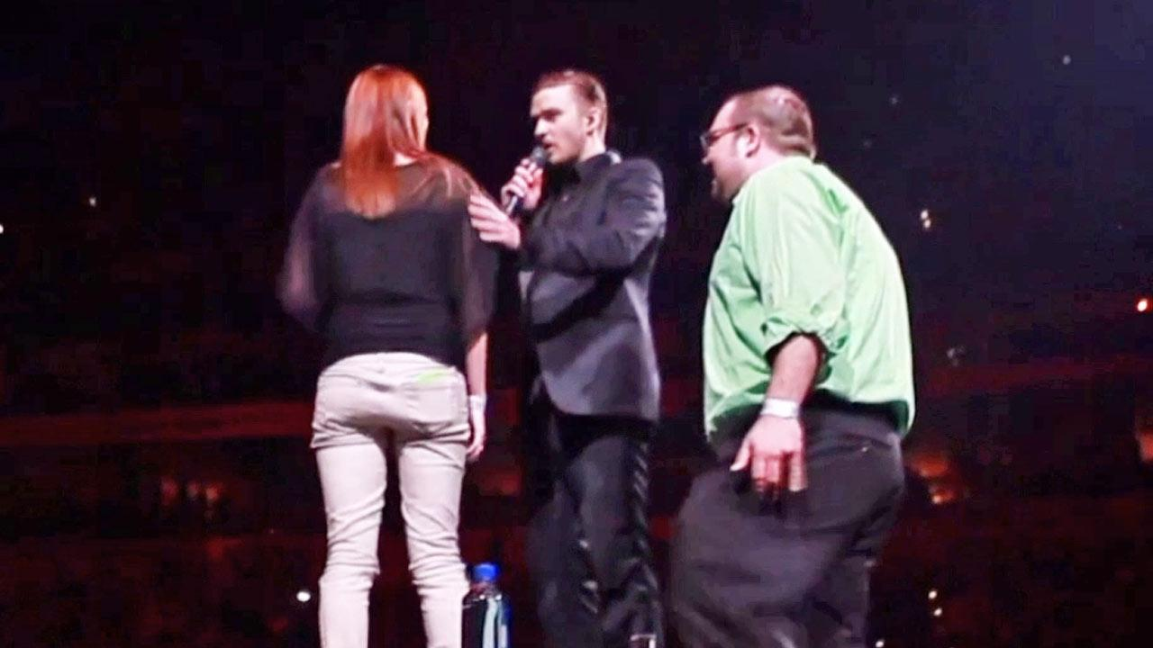 Justin Timberlake helps a fan propose to his girlfriend on stage at a concert in Louisville, Ky.