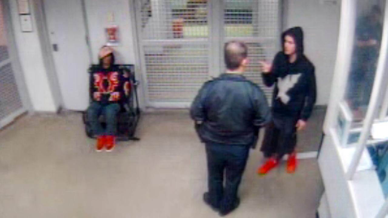 Singer Justin Bieber, right, gestures to a police officer while under arrest at the Miami Beach police in Miami Beach, Fla in this Jan. 23, 2014 video frame grab.