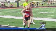 Ill. twin Claire Gruenke carries her twin sister Chloe to the finish line in this undated file photo.
