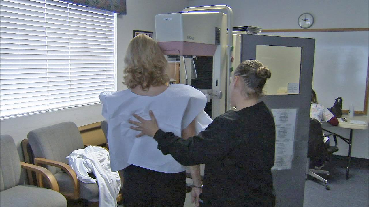 A woman is seen getting a mammogram.