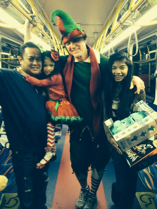 The Gloriani Family from Cerritos poses with Garth the Elf at Stuff-a-Bus in Cerritos on Friday, Nov. 22, 2013.