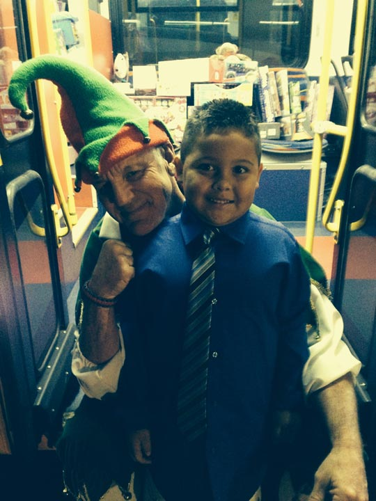 First grader Michael poses with Garth the Elf at Stuff-a-Bus in Cerritos on Friday, Nov. 22, 2013.