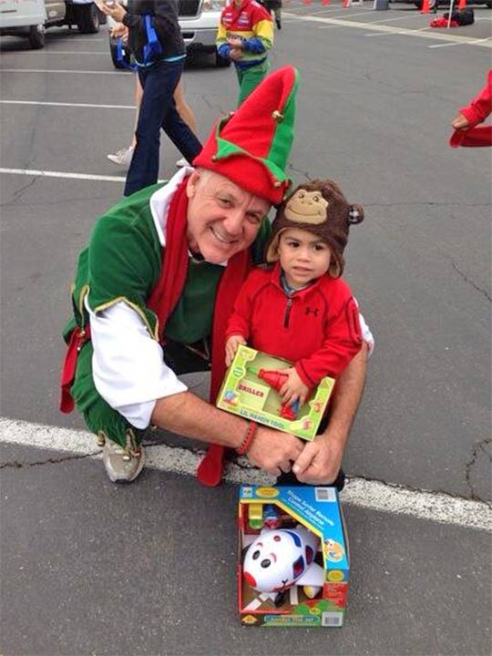 Garth the Elf poses with 2-1/2-year-old Frankie at the Stuff-A-Bus event at Los Cerritos Center in Cerritos on Friday, Nov. 22, 2013.