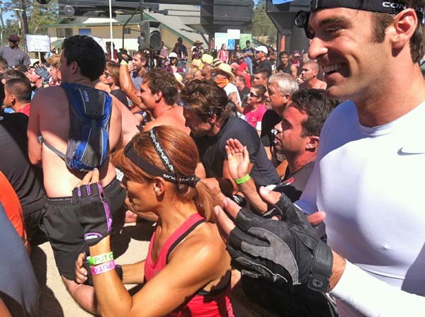 ABC7 reporters Eileen Frere (in pink) and Elex Michaelson (in white) attend a rally before the Tough Mudder event begins on Saturday, July 7, 2012.