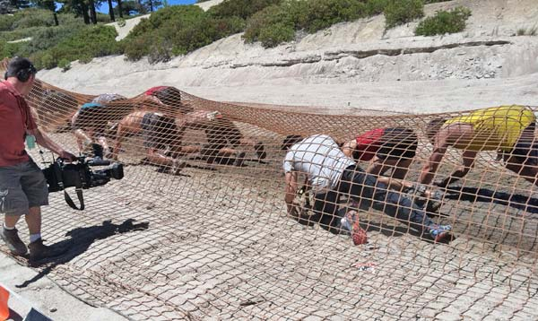 Tough Mudder participants crawl underneath a net...